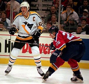Pittsburgh Penguins Mario Lemieux (66) looks for the puck as Florida Panthers Geoff Smith (25) guards him in the first period of the game in Pittsburgh Saturday, Dec. 30, 1995. Lemieux scored two goals in the first period. (AP Photo/Keith Srakocic)