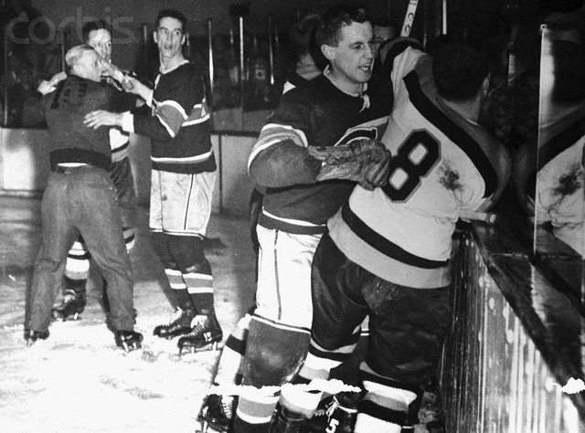 16 Mar 1955, Boston, Massachusetts, USA --- Photo shows a corner of the battlefield in Boston Garden during the bloody third period of the game between the Montreal Canadiens and the Boston Bruins last Sunday night. Maurice Richard, Canadiens' scoring star, flipped when he got a head cut from the stick of the Boston's Hal Laycoe. In the subsequent melee, Laycoe was hurt and linesman Cliff Thompson got banged on the head. In this scene, linesman Sam Babcock and Canadiens' Bert Olmstead are holding back Laycoe (rear) at left. At right, Canadiens' Bellueau is restraining Boston's Fleming Mackell (8). Concealed by the two wrestlers is Maurice Richard. --- Image by © Bettmann/CORBIS