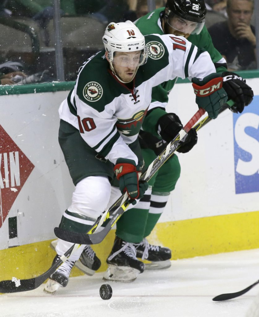 Minnesota Wild center Jordan Schroeder (10) takes control of the puck against Dallas Stars defenseman Stephen Johns (28) during the second period in Game 5 of a first-round NHL hockey Stanley Cup playoff series, Friday, April 22, 2016, in Dallas. (AP Photo/LM Otero)